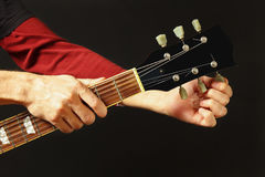 Hands of rock guitarist tunes the guitar on dark background. Hands of rock guitarist tunes the guitar on a dark background Stock Image