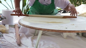 Hands roll the dough. Woman's hands roll the dough on a wooden table. Traditional Turkish cuisine stock video footage