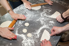 Hands rolling dough. Many hands rolling dough on table with flour royalty free stock photography