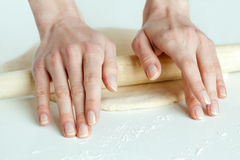 Hands rolling out dough in flour Stock Images