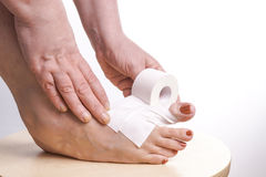 Hands rolling Therapeutic self adhesive tape on a Foot Royalty Free Stock Image