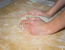 Hands rolls a ball of dough for pizza on homemade wooden Board with flour. Hands rolls a ball of dough for pizza on a homemade wooden Board with flour. Home Stock Photo