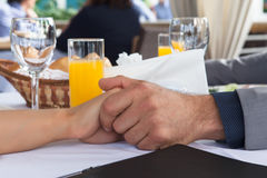 Hands of romantic couple over a restaurant table. Hands men and women of romantic couple over a restaurant table Royalty Free Stock Photo