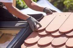 Hands of roofer laying tile on the roof. Installing natural red tile royalty free stock image