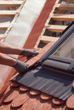 Hands of roofer laying tile on the roof. Installing natural red tile royalty free stock photo