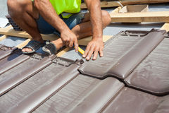 Hands of roofer laying tile on the roof. Installing natural red tile royalty free stock photography