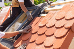 Hands of roofer laying tile on the roof. Installing natural red tile. Roof with mansard windows stock photography