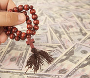 Hands with rosary. On a banknotes background Royalty Free Stock Photos