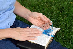 Hands with Rosary on Bible Stock Photos
