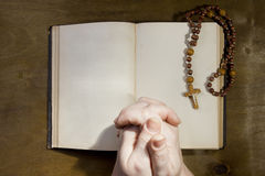 Hands with rosary and an old book Stock Photo