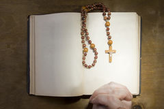 Hands with rosary and an old book Stock Images