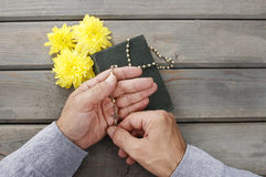 Hands with rosary over old Holy Bible Royalty Free Stock Photos