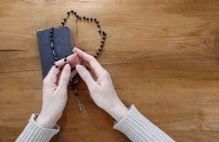 Hands with rosary over old Holy Bible. Wooden background Stock Photo