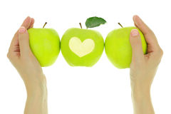 Hands with a row of green apples Royalty Free Stock Images