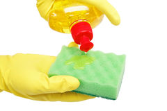 Hands in rubber gloves with a bottle and sponge. Hands in rubber gloves with a bottle of detergent and sponge on a white background. The detergent is poured on a Stock Image