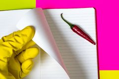 Hands in rubber gloves carefully turn over the page of an empty magazine and open burning red pepper. Bright pink and yellow