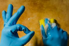 Hands in rubber gloves cleaning the surfaces of ceramic tiles, s. Afe and hygienic cleaning, keeping the house clean royalty free stock photo