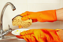 Hands in rubber gloves with sponge and dirty plate over the sink in kitchen Royalty Free Stock Photography
