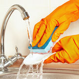 Hands in rubber gloves with sponge wash dirty dishes under running water Royalty Free Stock Photo