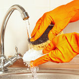 Hands in rubber gloves with sponge wash dirty plate under running water Royalty Free Stock Photo