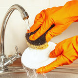 Hands in rubber gloves with sponge wash dishes under running water Stock Image