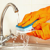 Hands in rubber gloves wash the dirty plate under running water in kitchen Stock Images