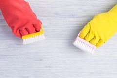 Hands in rubber yellow and red gloves washed with brushes light gray wooden floor royalty free stock photo