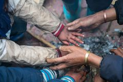 Hands of rural minority people warming up around the fire during the cold weather days in mountaious region in Vietnam.  Royalty Free Stock Photo