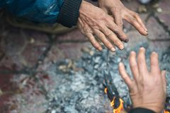Hands of rural minority people warming up around the fire during the cold weather days in mountaious region in Vietnam.  Royalty Free Stock Photography