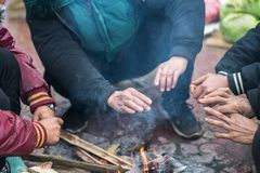Hands of rural minority people warming up around the fire during the cold weather days in mountaious region in Vietnam.  Royalty Free Stock Photos