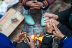 Hands of rural minority people warming up around the fire during the cold weather days in mountaious region in Vietnam.  Royalty Free Stock Image