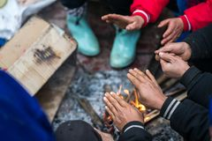 Hands of rural minority people warming up around the fire during the cold weather days in mountaious region in Vietnam.  Stock Photo