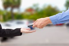 Hands of sale man giving a car key to woman - business concept. Hands of sale man giving a car key to woman - business concept Royalty Free Stock Images