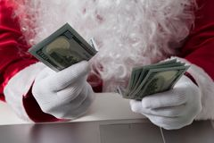 Hands of Santa Claus holding money, dollars. Counting paper currency, payment, shopping concept royalty free stock photos