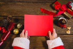 Santa Claus holding blank red paper. Hands of Santa Claus holding blank red paper royalty free stock photos
