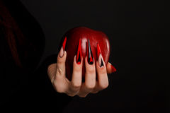 Hands with scary nails manicure holding poisoned red apple. On black background stock image