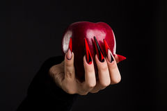 Hands with scary nails manicure holding red apple. Isolated on black background stock photography