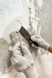 Hands scraping off old wallpaper with spatula Stock Photography