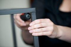 Hands screw together a piece of metal furniture. Hands screw together a piece of furniture Stock Photos