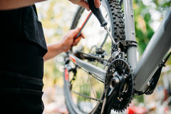 Hands with screwdriver repair shifter, bike repair. Male person hands with screwdriver repair front speed shifter. Professional bicycle mechanic. Cycle workshop Stock Images