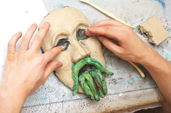 Hands sculpting plasticine form of face Stock Image