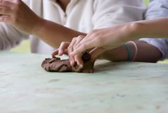 Hands of the sculptor. Manufacturing from clay of small things Stock Image