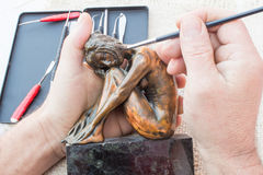 Hands of sculptor hold copper sculpture and clean it with brush Royalty Free Stock Image
