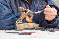 Hands of sculptor hold copper sculpture and clean it with brush Stock Image