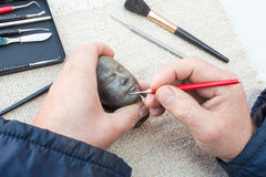 Hands of sculptor making sculpture head using tools Royalty Free Stock Images