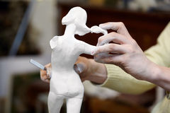 Hands of sculptor works with statuette. Royalty Free Stock Photography