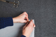 Hands of seamstress fixing template to fabric Stock Images