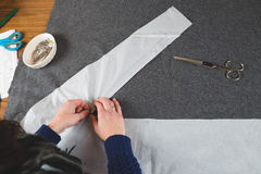 Hands of seamstress fixing template to fabric Royalty Free Stock Photos