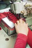 Hands of A Seamstress Stitching Red Cloth on Sewing Machine Royalty Free Stock Images