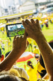 Hands of senior adult photographing Bersih 4 rally. Kuching, Malaysia - August 29, 2015: Photographing crowds at the Bersih 4.0 rally in Song Kheng Hai rugby Royalty Free Stock Photography
